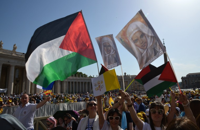 Image: Pilgrims wave Palestinian flags before a holy mass in St Peter's square for the canonization of four blessed nuns, whose two lived in Ottoman Palestine, on May 17, 2015 in Vatican.