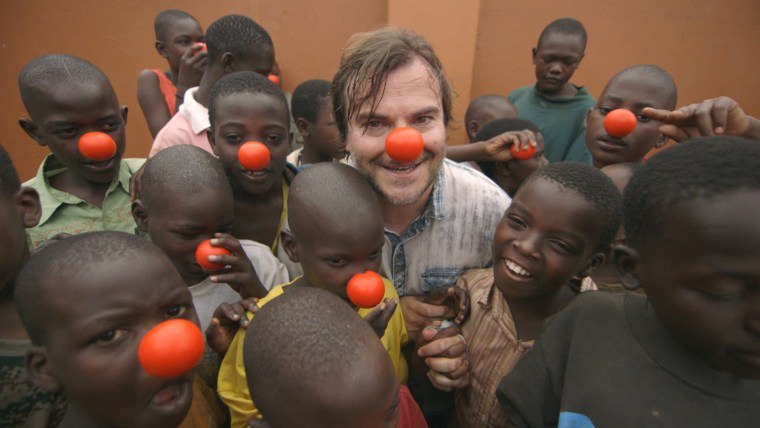 Jack Black wears a red nose alongside children in a slum in Uganda to raise awareness of kids living in poverty
