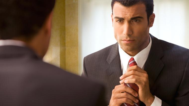Businessman adjusting his red tie