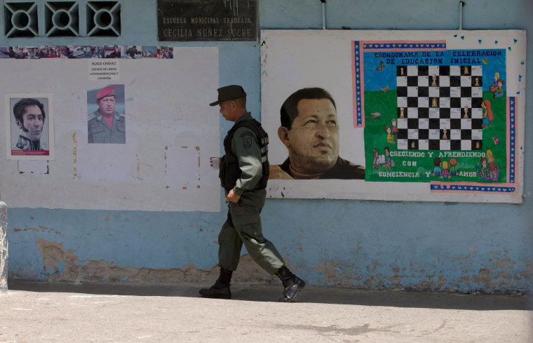 A Bolivarian National Guard officer walks near images of the late Venezuelan President Hugo Chavez and Independence hero Simon Bolivar, left, at a poll station in Caracas, Venezuela, Sunday, May 17, 2015.