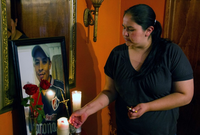 The sister of Mexican Ruben García Villalpando --who was fatally shot by a police officer in Tarrant County, TX,  lights a candle next to a portrait of her brother at her house, in the town of Nuevo Porvenir, in Durango State on February 28 2015.