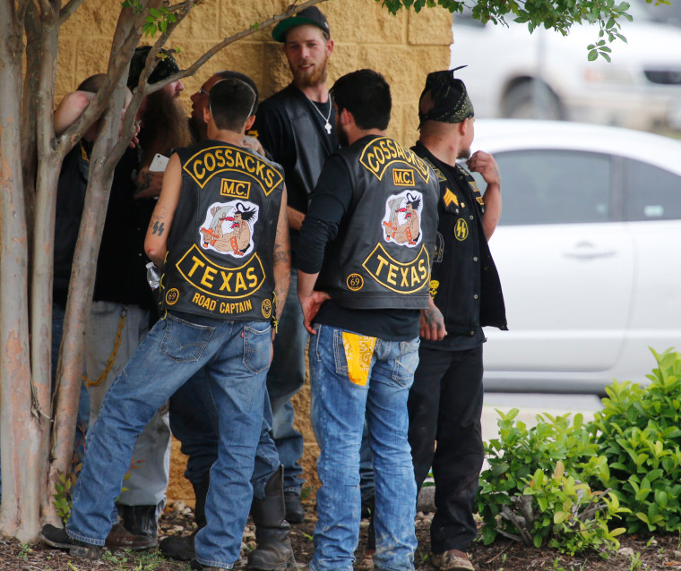 Image: Bikers congregate against a wall while authorities investigate a Twin Peaks restaurant