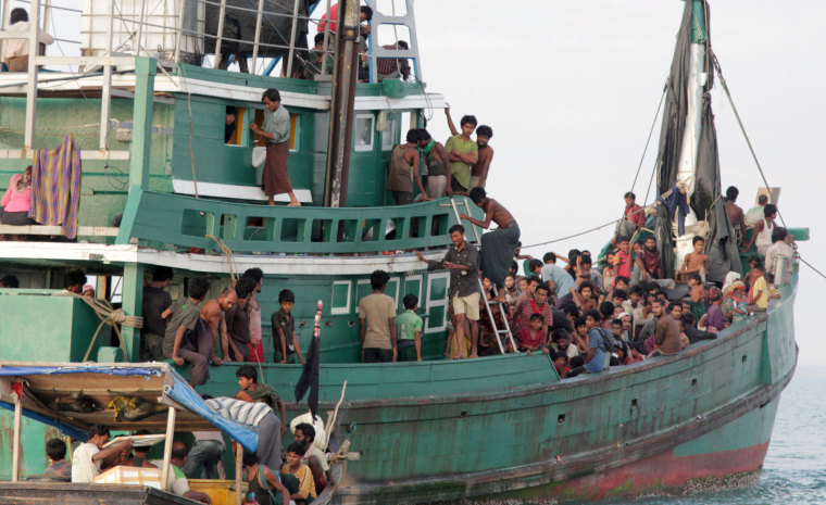 Image:Migrants sit on their boat as they wait to be rescued by Acehnese fishermen