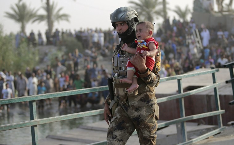 An Iraqi soldier carries a displaced child from Ramadi on the outskirts of Baghdad, Iraq May 19, 2015.