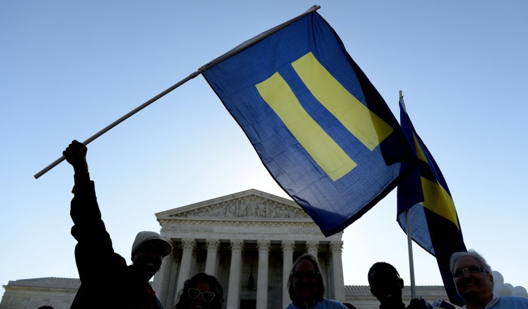Protesters hold pro-gay rights flags outside the US Supreme Court on April 28, 2015 in Washington, D.C.