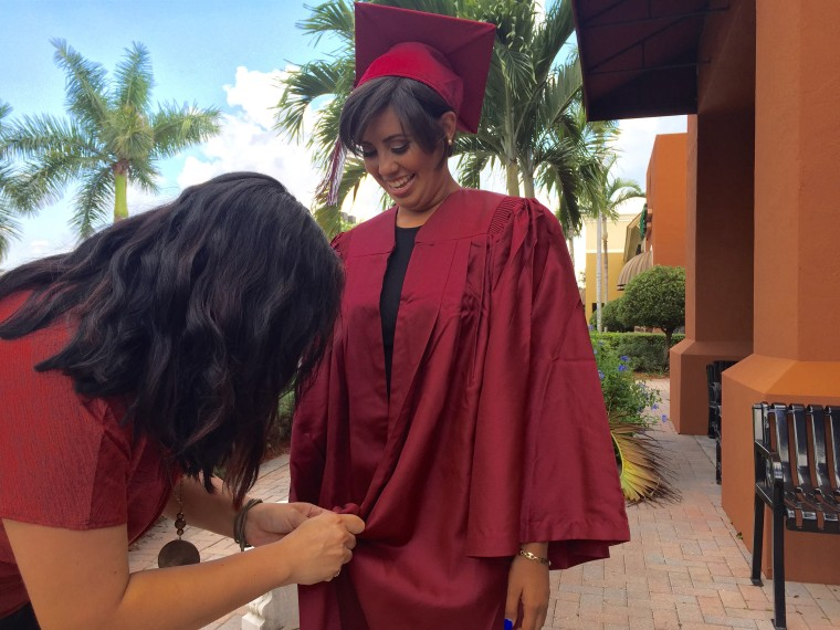 Mentor Julie Khanna adjusts Genesis' graduation gown before the ceremony.