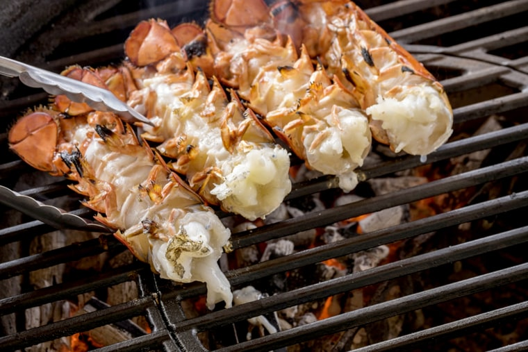 Lobster tails cooking over charcoal