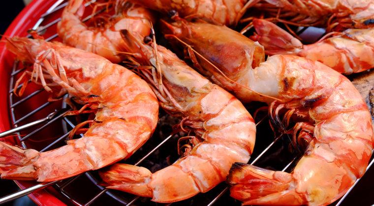 Grilled shrimp arranged on a large plate.