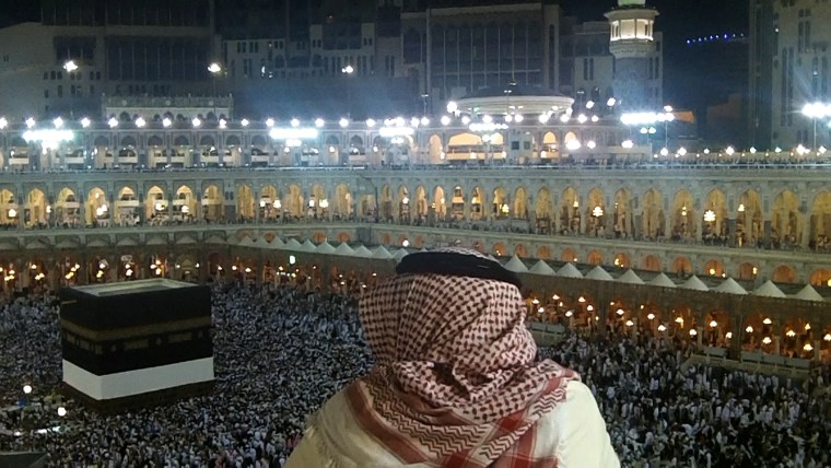 A man is seen at night overlooking the crowds circling the Kaaba.