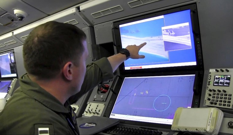 Image: Still image from United States Navy video shows a U.S. Navy crewman aboard a surveillance aircraft viewing a computer screen purportedly showing Chinese construction on the reclaimed land of Fiery Cross Reef in the disputed Spratly Islands