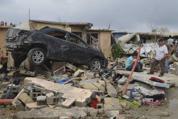 Image: Residents stand outside their damaged house after a tornado hit the town of Ciudad Acuna