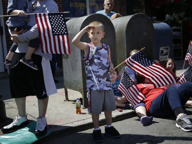 Image: Rocco Struncius salutes as soldiers walk by during a Memorial Day parade in the Glenwood neighborhood of New York