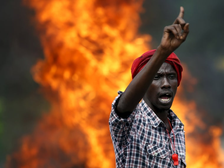 Image: A protester gestures in front of a burning barricade during a protest
