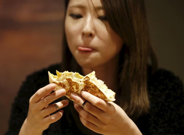 Image: A woman eats a taco at Taco Bell