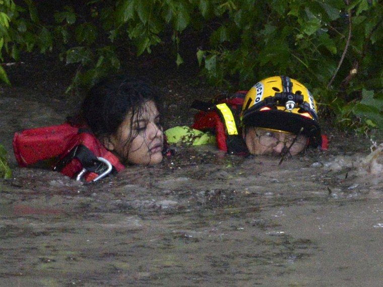 Image: San Marcos Firefighter Jay Horton rescues a woman from in flood waters in San Marcos Texas