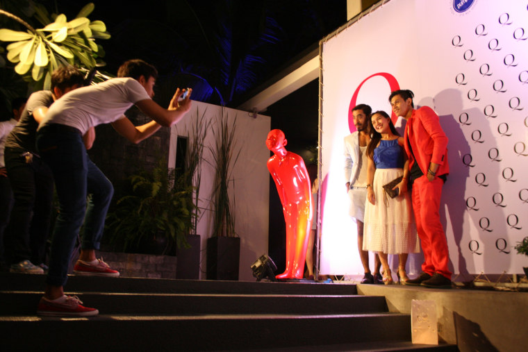 People get their photo taken at the launch party for Q Cambodia, the country's first print magazine geared toward the lesbian, gay and transgender community.