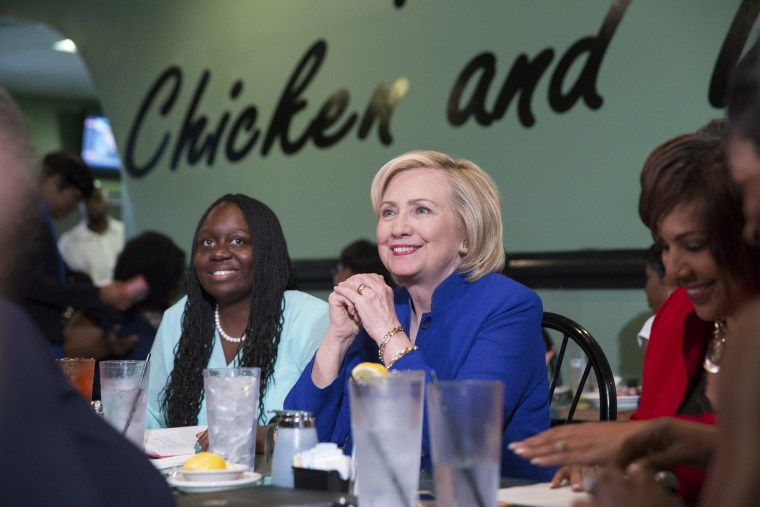 Image: Democratic presidential candidate Clinton talks with people assembled to meet her while sitting with business leaders at Kiki's Chicken and Waffles restaurant in Columbia