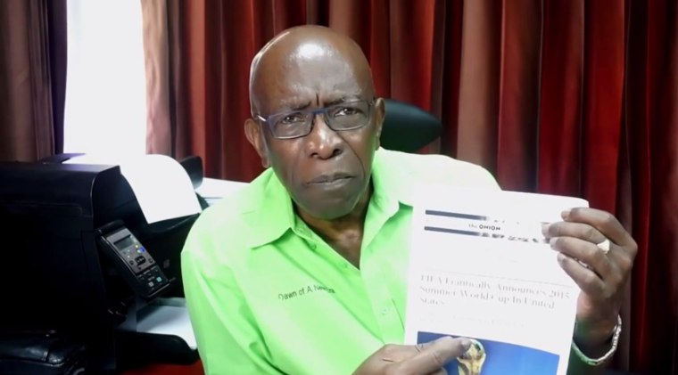 Former FIFA official Jack Warner holds up an article from the Onion, satirical paper that said the World Cup would be held in the United States in 2015 instead of in RUssia in 2018.