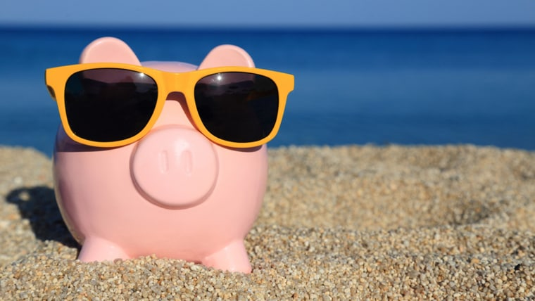 Summer piggy bank with sunglasses on the beach;