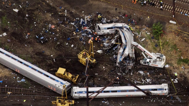 Image: Emergency workers look through the remains of a derailed Amtrak train in Philadelphia, Pennsylvania