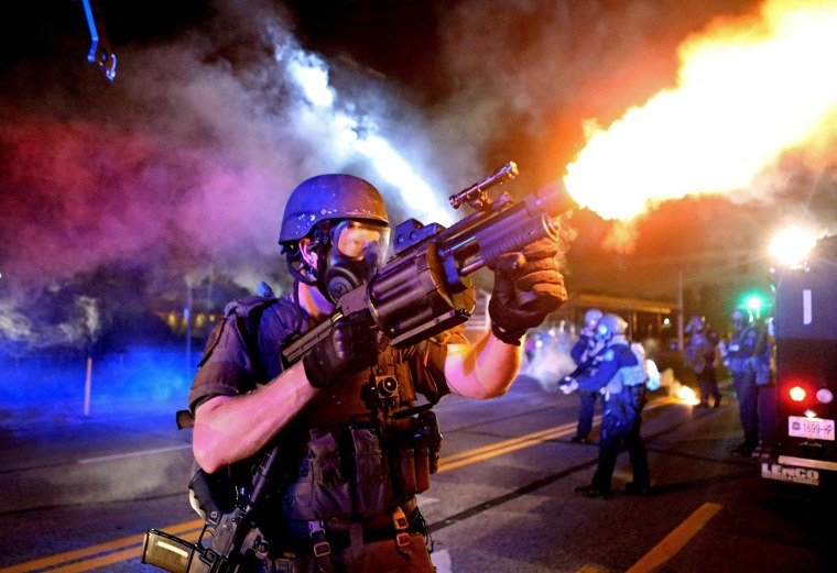 Image: A member of the St. Louis County Police tactical team fires tear gas into a crowd of people in response to a series of gunshots fired at police during demonstrations in Ferguson, Missouri