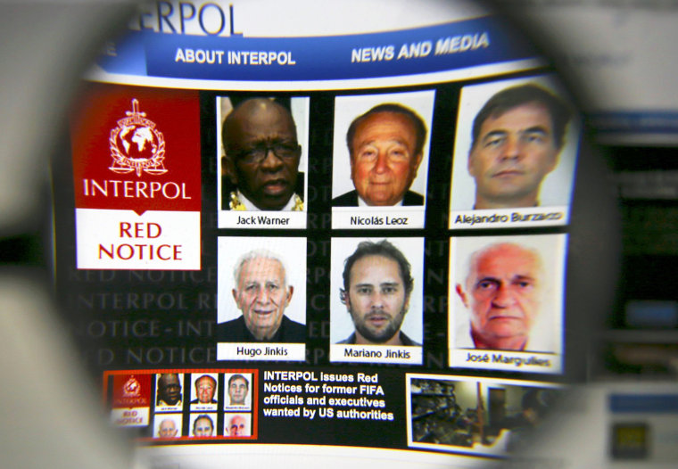Image: Interpol website is seen through a magnifying glass