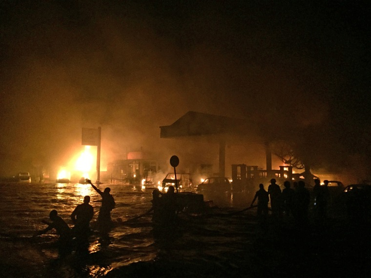 Firefighters and members of the public try to rescue survivors and douse the fire after a gas station in Ghana's capital blew up while many people were sheltering there from torrential rainfall and flooding.