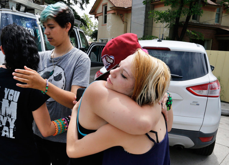 Image: Ciera Rogers, far right, receives condolences from her friend Sam Hinde