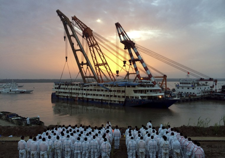 Image: Rescue workers stand on the river bank as the capsized cruise ship Eastern Star is pulled out of the Yangtze against sunset, in Jianli