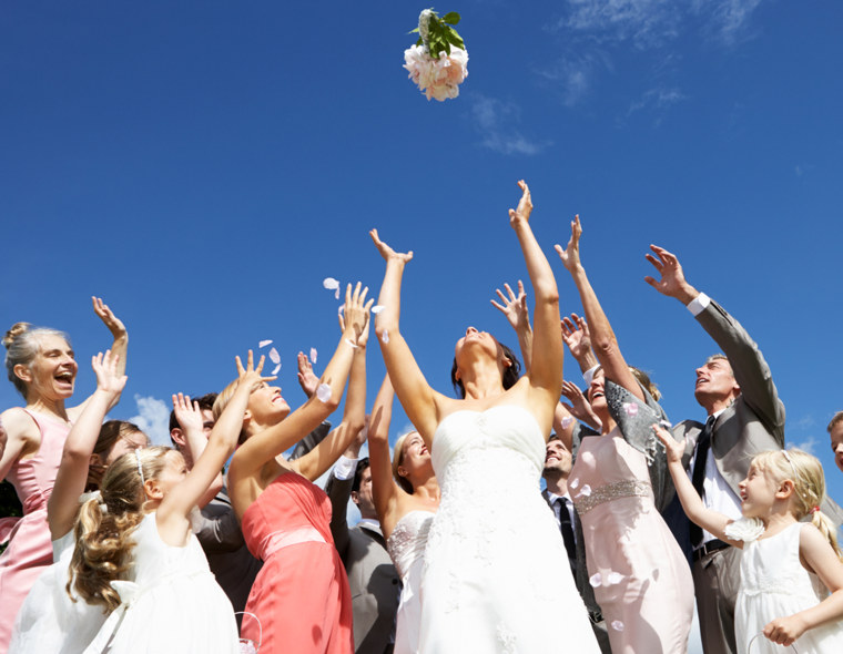 Bride Throwing Bouquet For Guests To Catch.