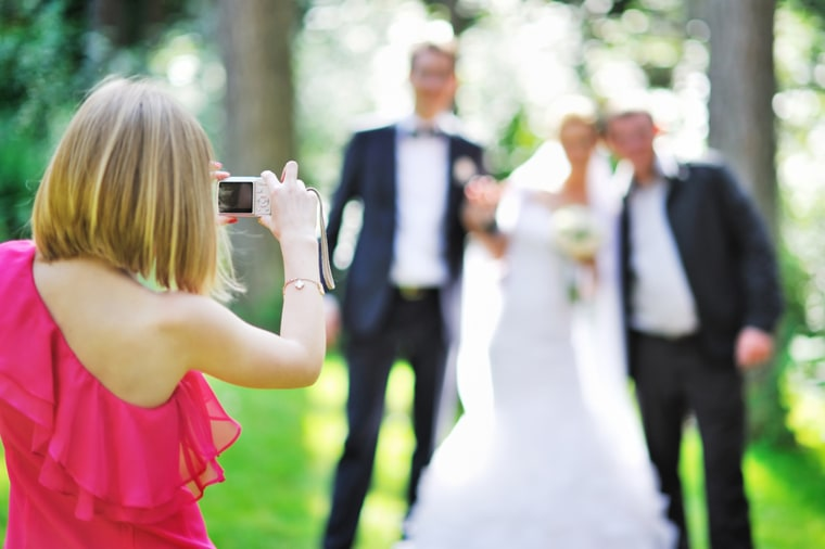Girl photographing guests at a wedding.