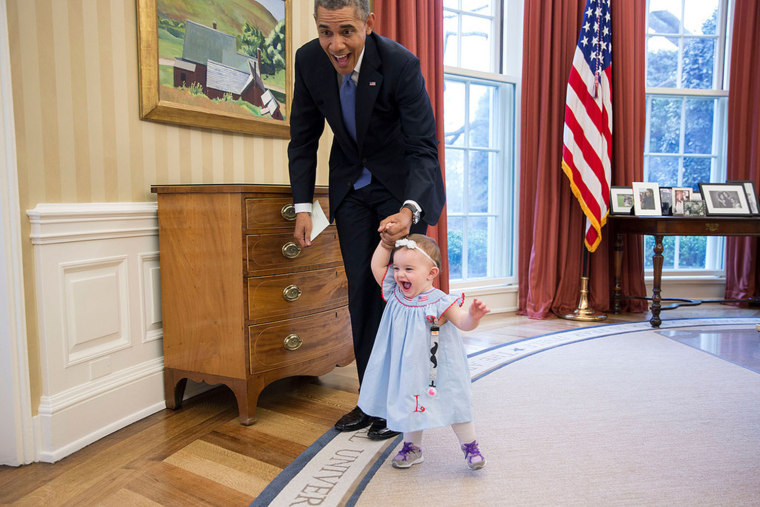 Obama plays with baby in Oval Office.