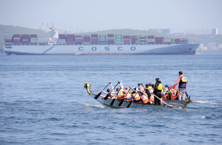 Image: Athletes compete in a Dragon boat pulling race in the Sea of Japan waters, with the COSCO Yantian cargo ship seen in the background, near the far eastern port of Vladivostok