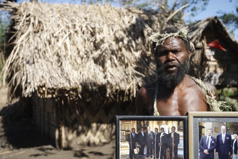 Image: Albi Nagia poses with photographs of Prince Philip in Yakel, Tanna island, Vanuatu.