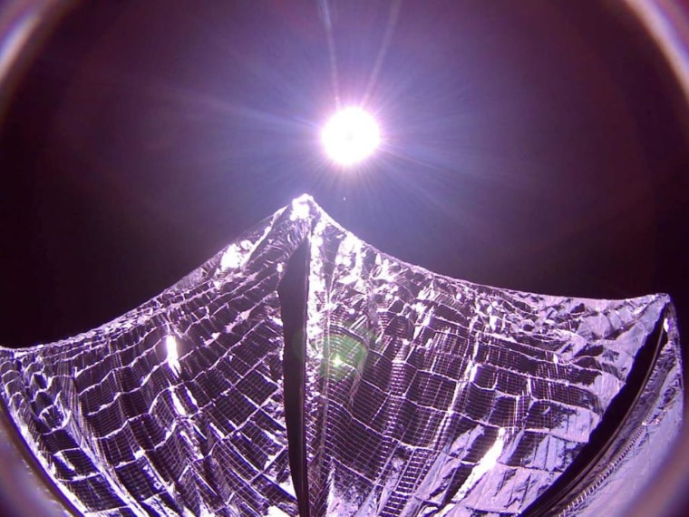 A picture transmitted from the LightSail solar sail spacecraft in orbit shows its reflective sails partially deployed, with the sun glaring in the background.
