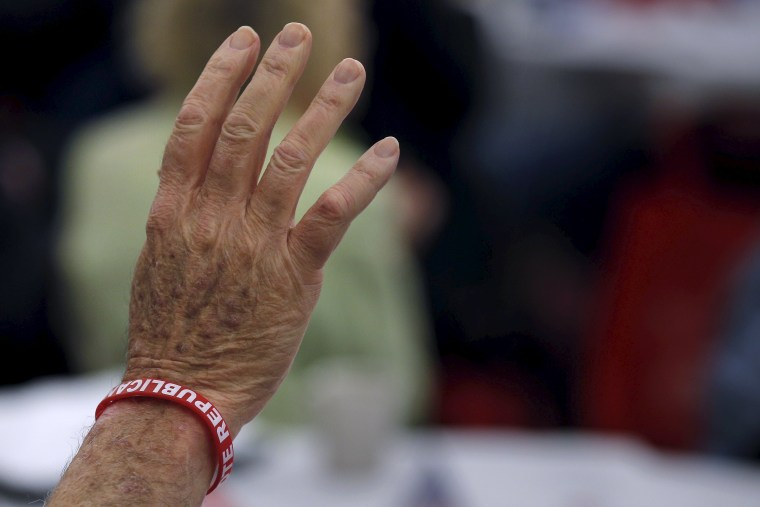 """Image: A U.S. veteran wearing a bracelet with the word \""""Republican\"""" on it raises his hand to be acknowledged at the First in the Nation Republican Leadership Conference in Nashua"""