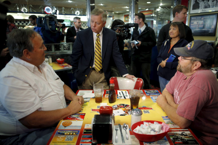 Image: Republican presidential candidate U.S. Senator Lindsey Graham (C) (R-SC) talks to diners during a campaign stop at MaryAnn's Diner in Derry