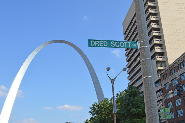 """""""Dred Scott Way"""" street sign hangs in front of the St. Louis Arch."""