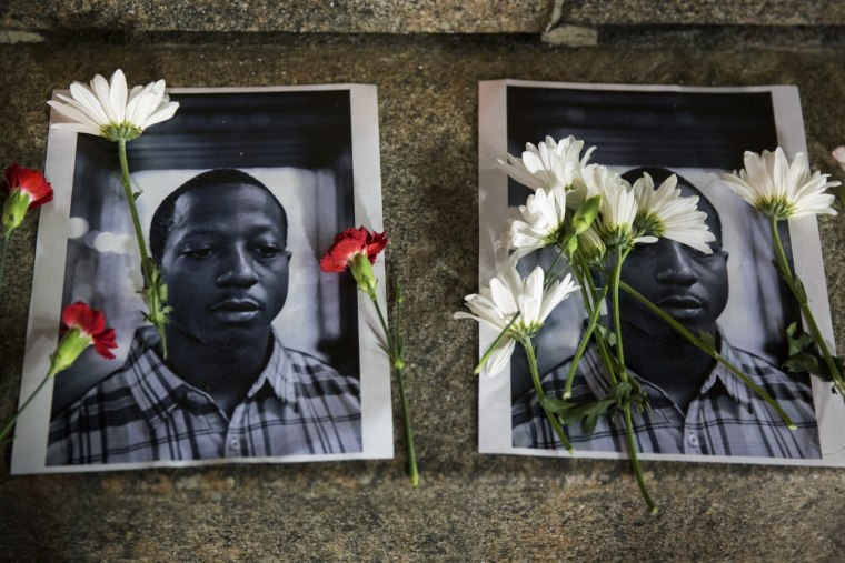 Image: Flowers rest on top of pictures of Browder in New York