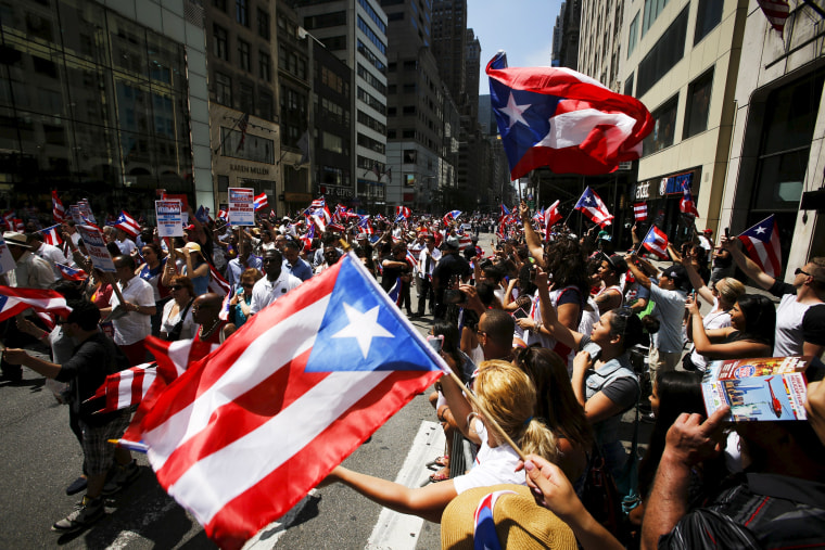 Image: People take part in the National Puerto Rican Day Parade on Fifth Avenue in Manhattan, New York