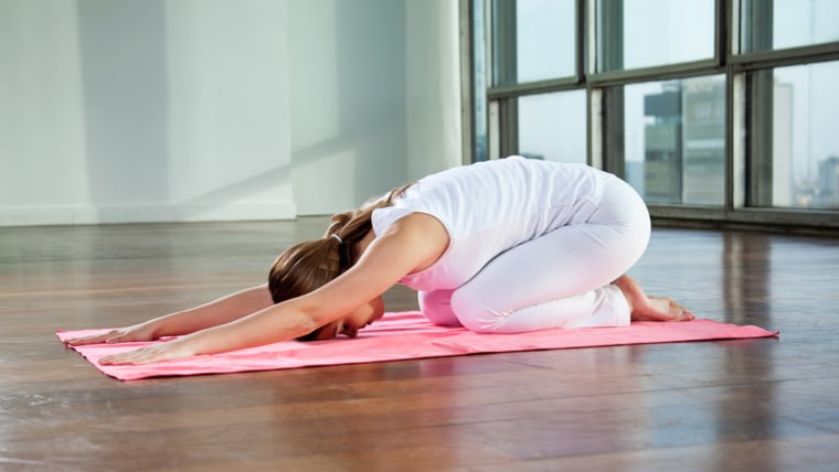 young woman sitting in child's pose on a yoga mat