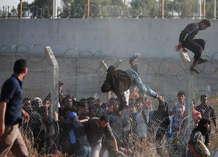 Image: Syrian refugees cross into Turkey from Syria