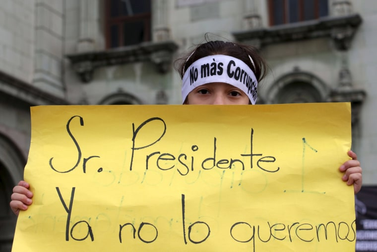 Image: A protester holds a sign during a demonstration demanding the resignation of Guatemalan President Otto Perez Molina in Guatemala City