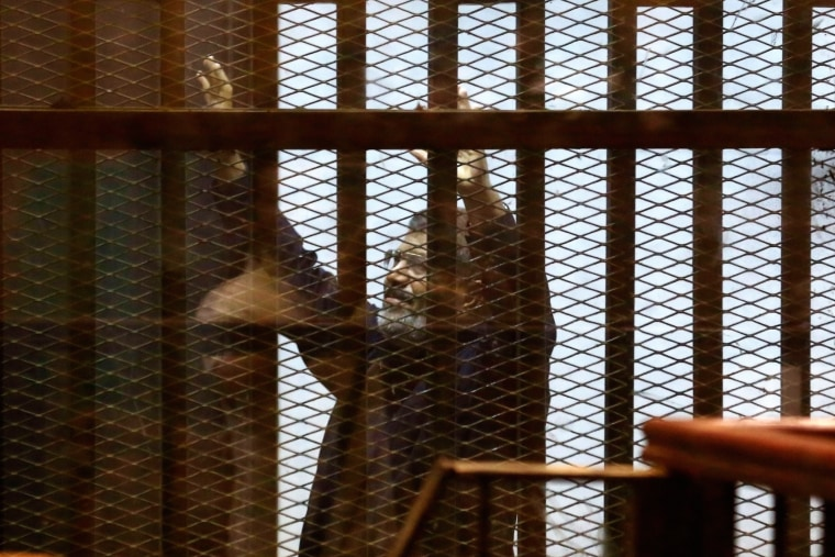 Image: Egypt's ousted Islamist President Mohammed Morsi gestures in a defendants cage