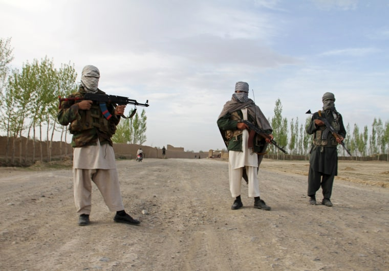 Image: Members of the Taliban stand at the site of the execution of three men in Ghazni Province
