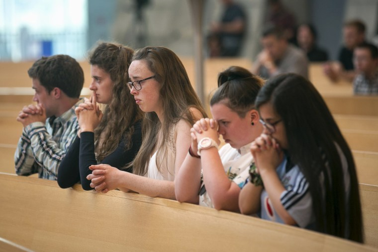 Image: Some young attendees sit in prayer during a special Mass for the victims of the Berkeley balcony collapse in Oakland, California