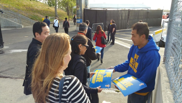 Wong passing out signs to fans at Oracle Arena during the 2015 playoffs.