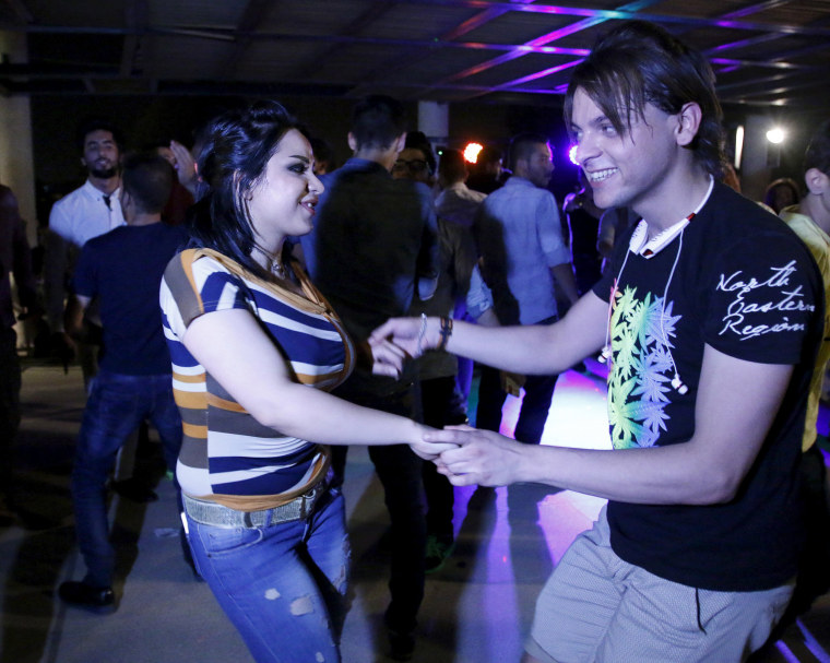 Image: Young people dance during a party at a hotel in Baghdad