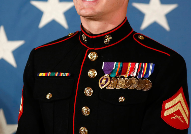 A retired  U.S. Marine Corps Corporal  stands before receiving the Medal of Honor from U.S. President Barack Obama on June 19, 2014