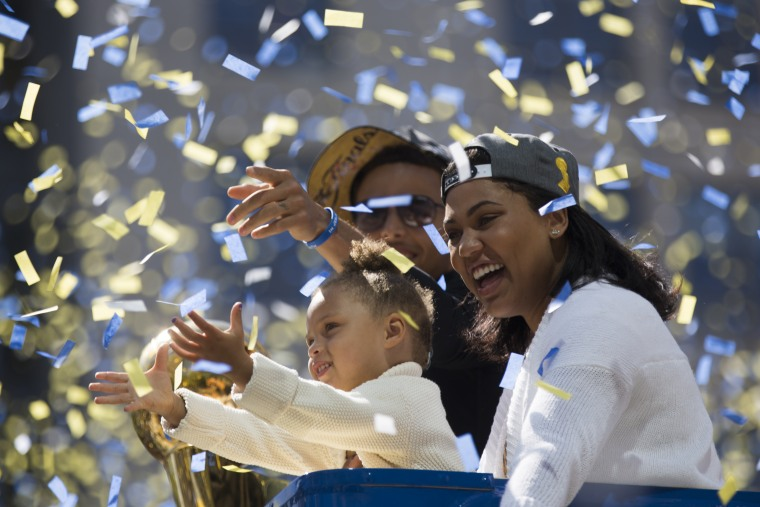 Stephen Curry, daughter Riley Curry (L) and wife Ayesha Curry (R) celebrate as confetti falls during the Golden State Warriors Victory Parade in Oakland, California.